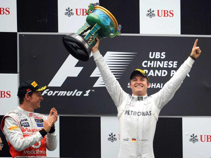 Nico Rosberg holds up the winner's trophy as third-placed Lewis Hamilton of Britain and second-placed Jenson Button of Britain applaud on the podium during the awards ceremony at the Shanghai International Circuit. (AFP/Liu Jin)