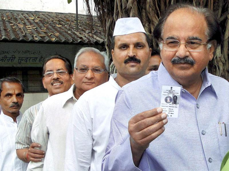 Delhi health minister AK Walia shows his voter ID card as he stands in a queue to cast his vote during MCD elections at Laxmi Nagar in East Delhi. PTI Photo