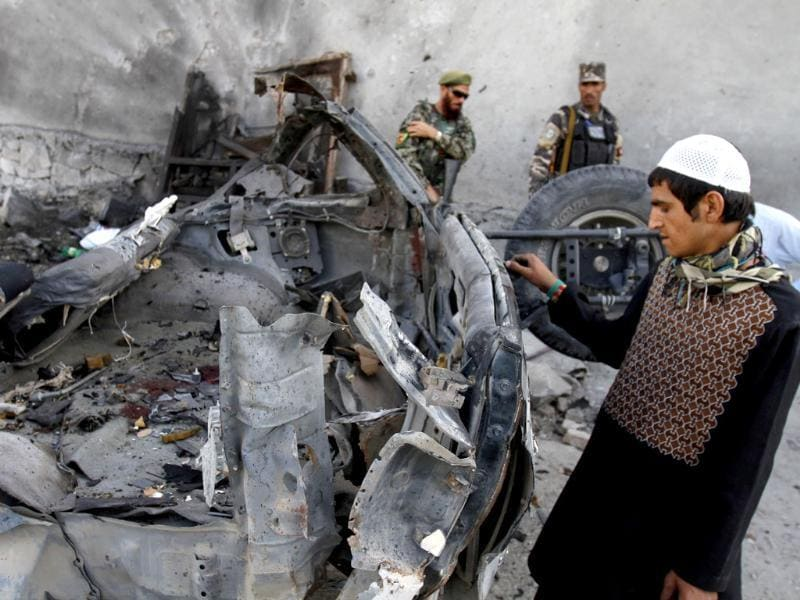 An Afghan man examines the remains of a car after three suicide bombers were killed before they reached Jalalabad airport, which security forces say was their target, in Jalalabad, east of Kabul, Afghanistan. AP/Rahmat Gul