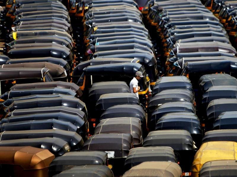 A pedestrian walks through parked three wheelers called auto rickshaws, during a strike in Mumbai. Auto rickshaw drivers went on a day long strike to protest against a lower than expected hike in fares. AP Photo/Rafiq Maqbool