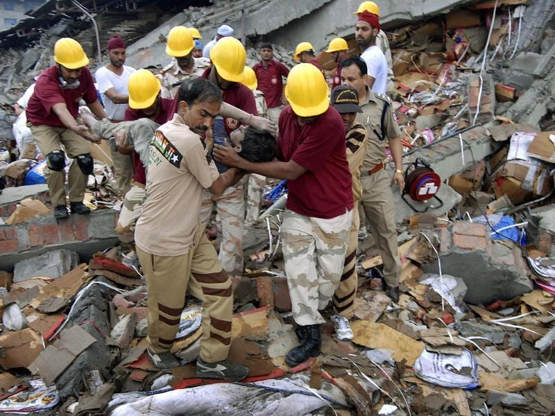 Rescue workers remove a worker from the debris of a collapsed factory in Jalandhar. (AP Photo/ Shammi Mehra)