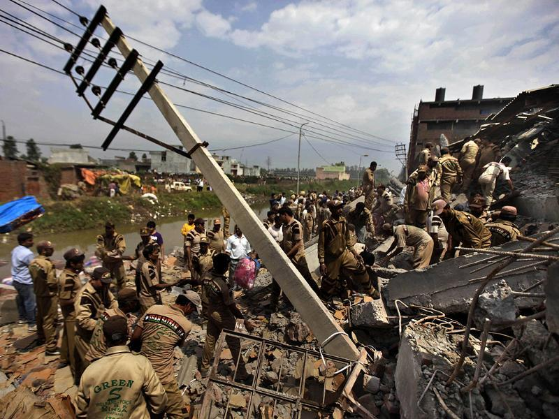 Rescue workers work at the site of a collapsed factory in Jalandhar. (AP Photo/ Altaf Qadri)