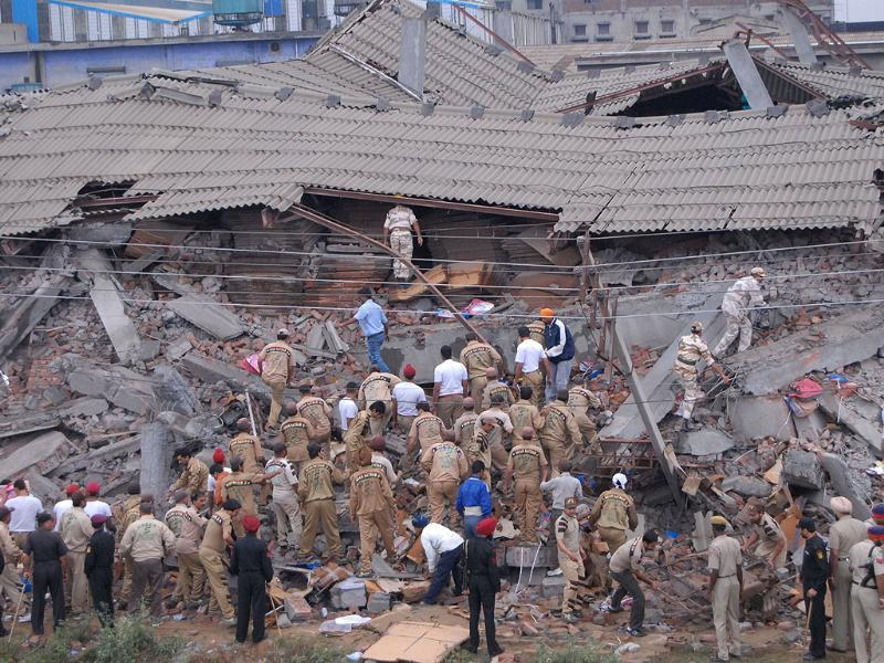 Emergency workers search through the debris of a collapsed building in Jalandhar. (AFP photo)