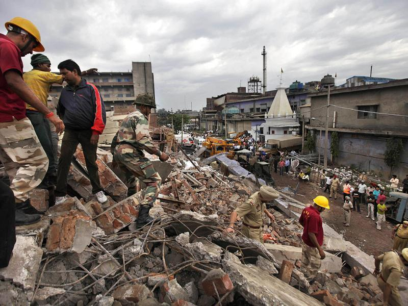 Rescue workers and Indian army soldiers climb down from the debris of a collapsed factory in Jalandhar. (AP Photo/ Altaf Qadri)