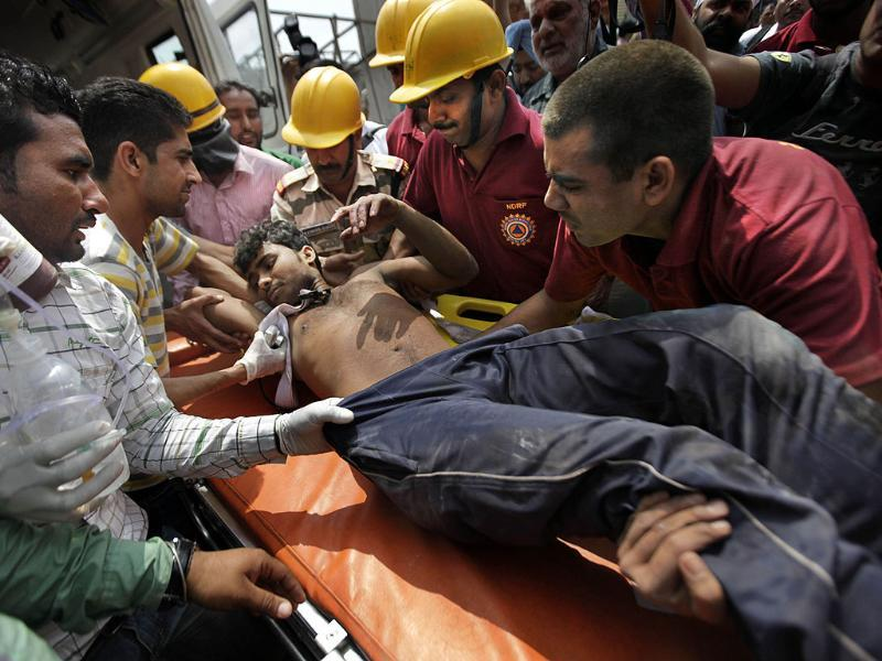 Workers remove a worker from the debris of a collapsed factory in Jalandhar. (AP Photo/ Altaf Qadri)