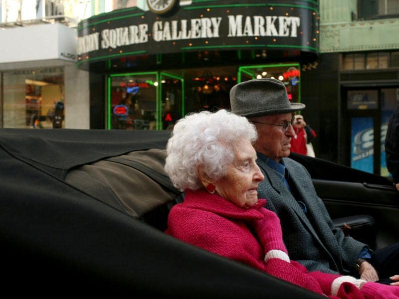 Winnie Hook (L), 106, and George Quilici, 107, two of the four known survivors of San Francisco's great earthquake and fire of 1906, ride in a parade to John's Grill for the city's annual survivors dinner in San Francisco, California. (Reuters/Robert Galbraith)