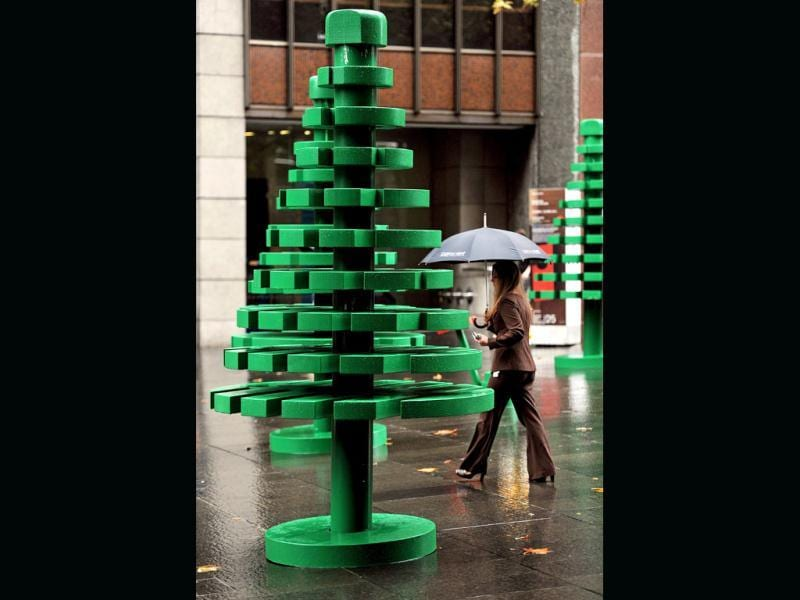 A woman (R) walks through a life-sized LEGO forest during a wet morning in Sydney to celebrate the 50th anniversary of the LEGO brick in Australia. (AFP photo/ Greg Wood)