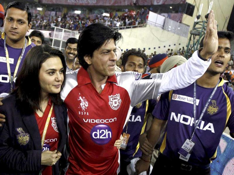 Bollywood stars Priety Zinta and Shah Rukh Khan wave after they exchanged their team T-shirts after the IPL-5 match between Kings XI Punjab and Kolkata Knight Riders in Mohali. PTI Photo/Aman Sharma