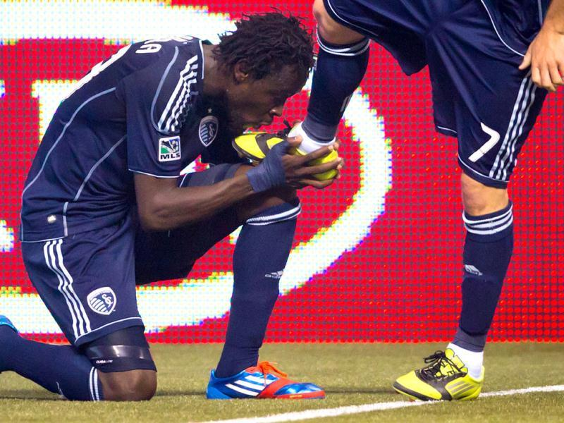 Sporting Kansas City's Kei Kamara, left, of Sierra Leone, kisses the boot of teammate Chance Myers after Kamara scored a goal against the Vancouver Whitecaps during second-half MLS soccer game action in Vancouver, British Columbia. (AP Photo/The Canadian Press, Darryl Dyck)