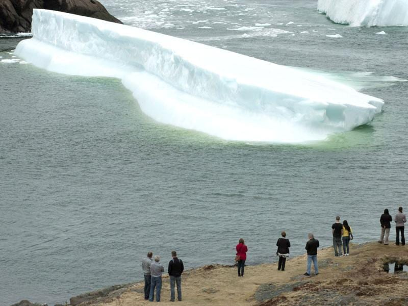 Sightseers line the shore as two icebergs sit grounded near St. John's, Newfoundland, and Labrador. (AP Photo)