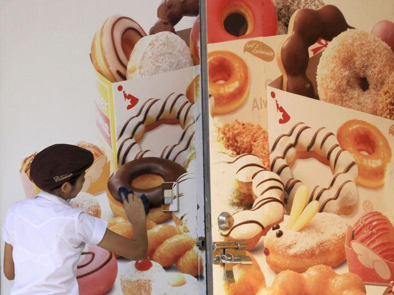 A worker cleans an advertising banner at a doughnut shop in Bangkok ,Thailand.(AP Photo/Sakchai Lalit)