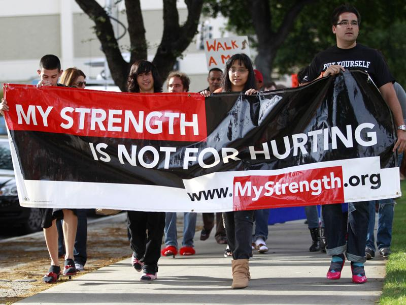 Participants, many wearing women's high heels, carry a sign during the 10th annual Walk A Mile In Her Shoes to raise awareness against sexual violence in Plaza De Cesar Chavez in San Jose, California. REUTERS/Stephen Lam