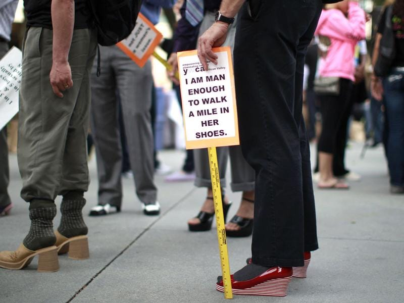 A man holds a sign while wearing a pair of women's high heels during the 10th annual Walk A Mile In Her Shoes to raise awareness against sexual violence in Plaza De Cesar Chavez in San Jose. REUTERS/Stephen Lam