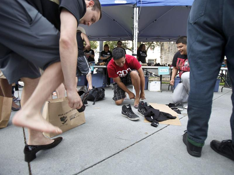 A group of men try on women's high heels during the 10th annual Walk A Mile In Her Shoes to raise awareness against sexual violence in Plaza De Cesar Chavez in San Jose, California. REUTERS/Stephen Lam