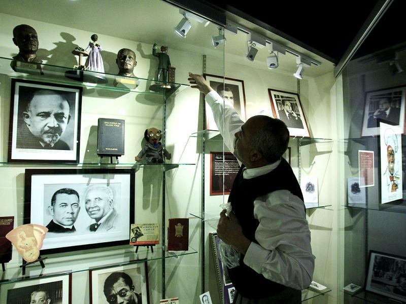 David Pilgrim, the founder and curator who started building the Jim Crow Museum of Racist Memorabilia, adjusts a display at the museum in Big Rapids, Mich. The museum says it has amassed the nation's largest public collection of artifacts spanning the segregation era, from Reconstruction until the civil rights movement, and beyond. AP Photo/Carlos Osorio