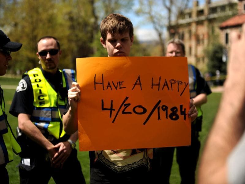 Colorado University senior Gabriel Kuettel holds up a sign at the Norlin Quad which was closed to crackdown on pro-marijuana protesters at the school in Boulder, Colo. A block-long line of protesters marched onto the University of Colorado, testing the school's determination to push the annual April 20 marijuana celebration off campus. (AP Photo/The Denver Post, Joe Amon)