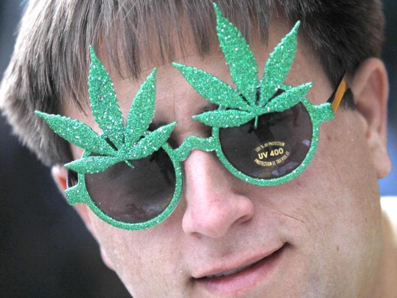 Brandon Dahl wears novelty sunglasses adorned with artificial marijuana leaves as he sells them across the street from a pro-marijuana rally at the University of Colorado in Boulder, Colorado. The University of Colorado clamped down on a huge annual marijuana fest on Friday by restricting access to the school and a field where the
