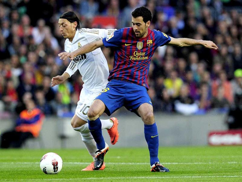 Real Madrid's German midfielder Mesut Ozil (L) vies with Barcelona's midfielder Sergio Busquets (R) during the Spanish League El clasico football match Barcelona vs Real Madrid at the Camp Nou stadium in Barcelona. (AFP Photo/Josep Lago)