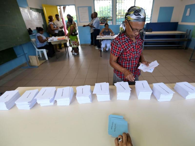 A woman picks up ballots prior voting at a polling station in La Possession in the French Indian ocean island of La Réunion, for the first-round poll of French 2012 presidential election. AFP/Richard Bouhet