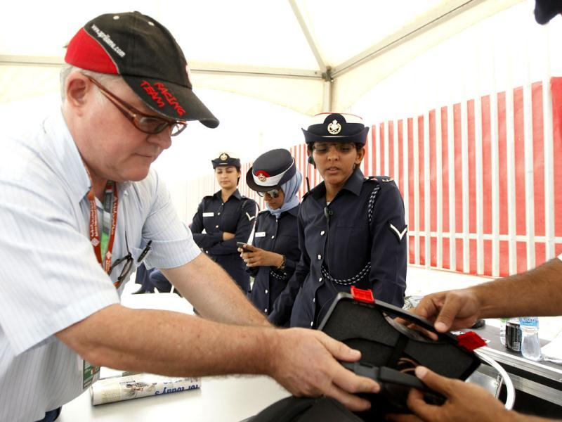 Bahraini policemen check a reporter's bag at the entrance gate prior to the start of the Bahrain Formula One Grand Prix at the Formula One Bahrain International Circuit in Sakhir, Bahrain. (AP Photo/Luca Bruno)