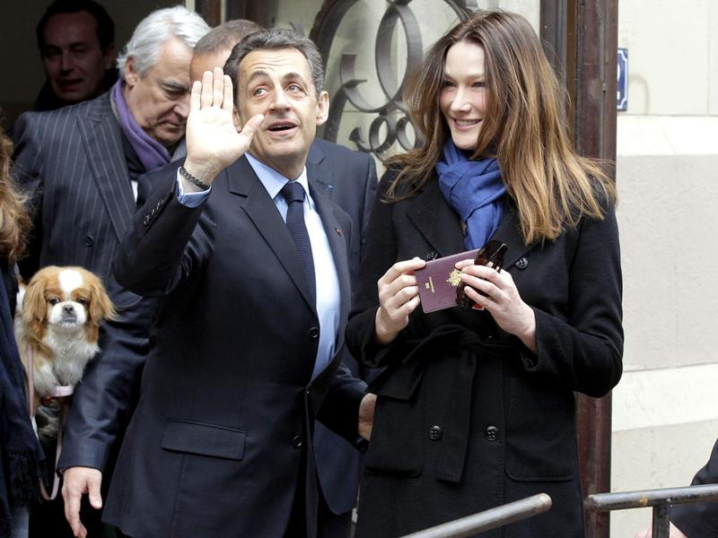 French President and UMP candidate Nicolas Sarkozy and his wife Carla Bruni-Sarkozy leave after casting their votes in the first round of French presidential elections in Paris, France. AP Photo/Michel Euler