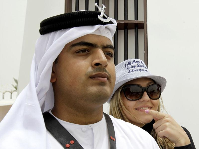 A F1 fan poses for picture with a Bahraini policeman wearing traditional uniform ahead of the Formula One Grand Prix at the Bahrain International Circuit in Sakhir, Bahrain. (AP Photo/Hassan Ammar)