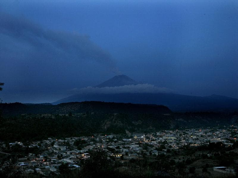 Lights illuminate the Mexican town of Xalitzintla as the looming Popocatepetl Volcano spews ash and steam during an early morning eruption. AP Photo/Marco Ugarte
