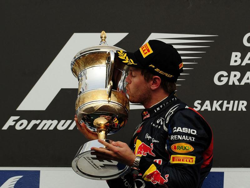 Red Bull Racing's German driver Sebastian Vettel kisses the cup on the podium at the Bahrain International circuit in Manama after the Bahrain Formula One Grand Prix. (AFP Photo/Dimitar Dilkoff)