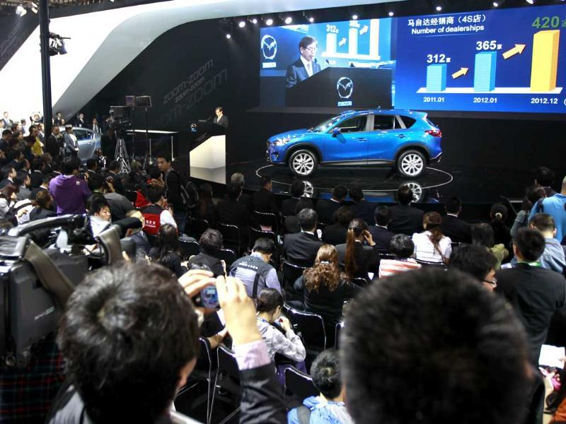 Media attend a press conference by Mazda as the company launches new SUV CX-5 at the Beijing International Auto Exhibition in Beijing, China. AP Photo/Vincent Thian