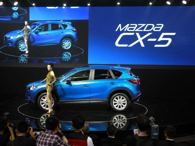 A model poses with Mazda's newly launched SUV CX-5 at the Beijing International Auto Exhibition in China. AP Photo/Vincent Thian