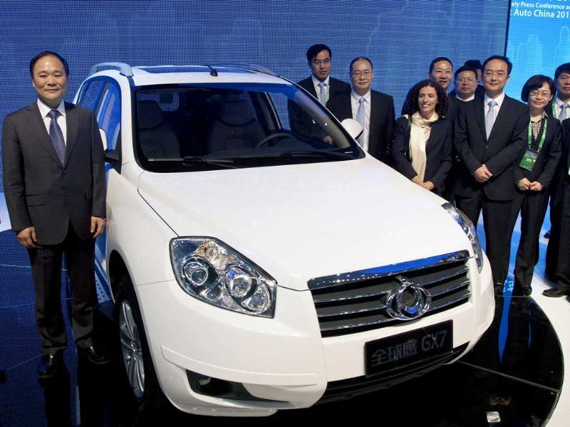 Geely Holding Group chairman Li Shufu (L) stands next to the new Geely Gleagle GX7 model after it was unveiled at the Beijing International Automotive Exhibition in China. AP Photo/Andy Wong