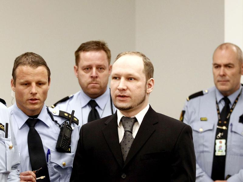 Terror and murder charged Anders Behring Breivik is surrounded by police officers in the courtroom prior to the opening of day 6 of the trial in Oslo. AFP Photo: Lise Aserud/Pool