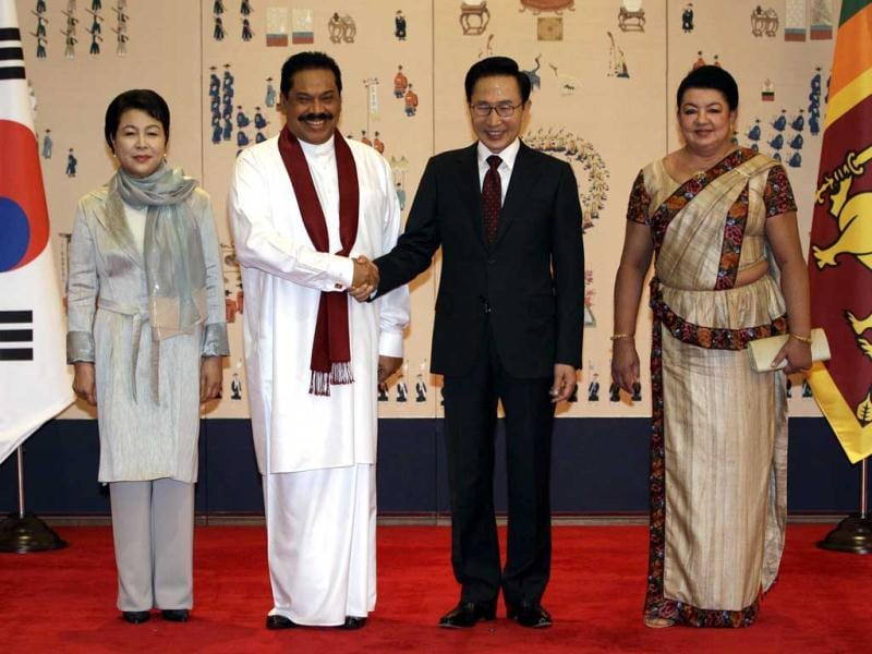 South Korean President Lee Myung-bak (C-R) and Sri Lankan President Mahinda Rajapaksa (C-L) shake hands as Lee Myung-bak's wife Kim Yoon-ok (L) and Mahinda Rajapaksa's wife Shiranthi Rajapaksa (R) look before their summit at the Blue House, the official presidential house, in Seoul. Rajapaksa is on a four day official visit to South Korea. AFP Photo/Pool/Lee Jin-man