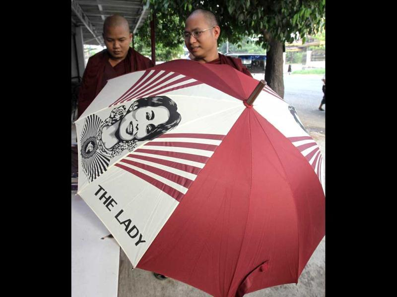A Buddhist monk buys an umbrella with an image of Myanmar pro-democracy leader Aung San Suu Kyi at a souvenir shop outside her National League for Democracy headquarters in Yangon, Myanmar. Suu Kyi's opposition party refused to take its new seats in parliament Monday because of a dispute over one word in the lawmakers' oath, but party officials said the issue would be overcome soon and the Southeast Asian nation's president also said a revision was possible. AP Photo/Sakchai Lalit
