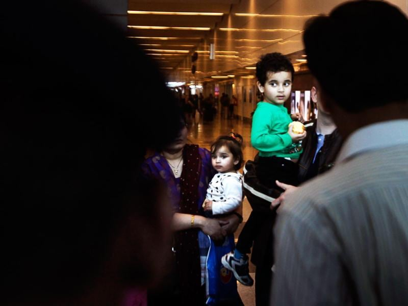 Abhigyan Bhattacharya, 3, center right and his sister Aishwarya arrive at the airport in New Delhi. AP/Manish Swarup