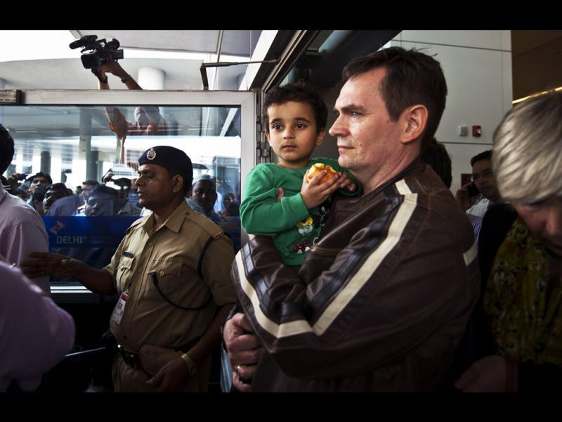 Three year old Abhigyan Bhattacharya is held by his Norwegian foster father upon their arrival at IGI airport in New Delhi. AFP/Prakash Singh