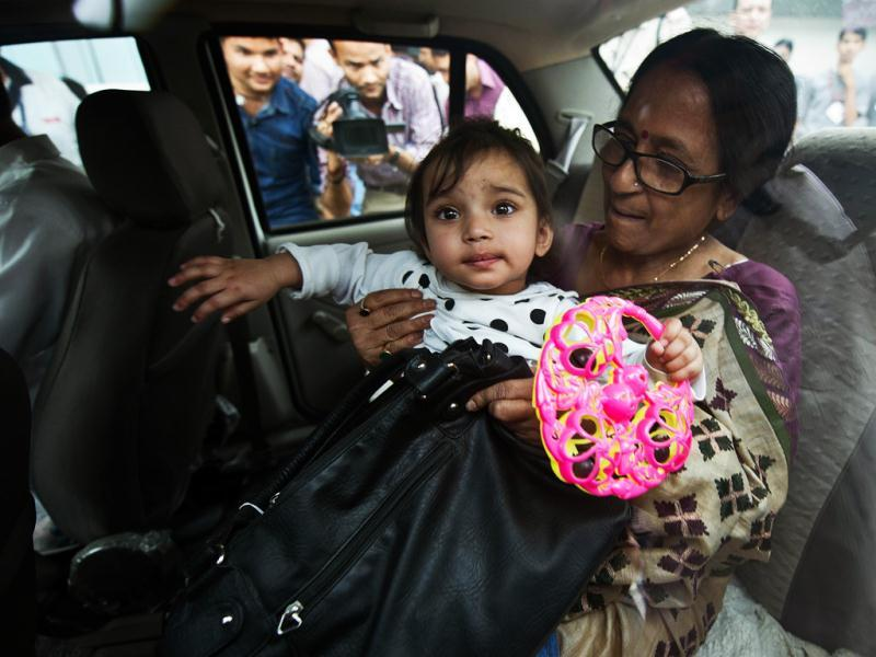 One year old Aishwarya Bhattacharya is held by her grandmother in a car at IGI airport in New Delhi, shortly after her arrival. AFP/Prakash Singh