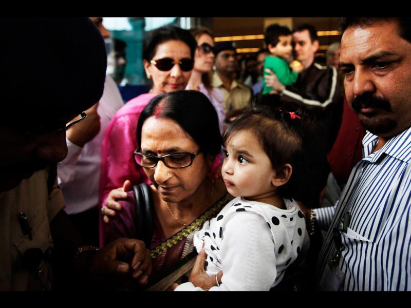 Aishwarya Bhattacharya, 1, is carried by her grandmother as she arrives at the airport in New Delhi. Aishwarya and her brother, caught in a custody row in Norway, returned home to India after a court ruled they be handed over to their uncle. AP/Manish Swarup