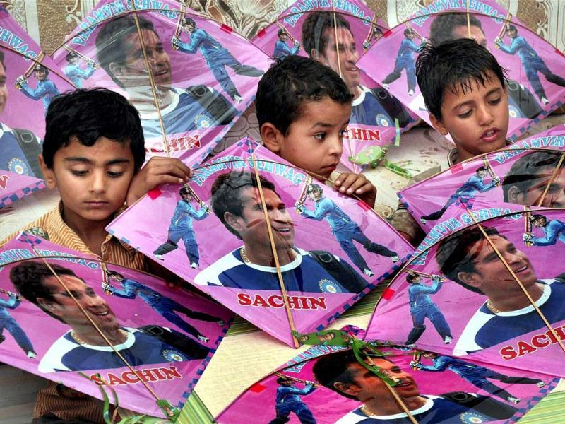 Children hold kites bearing pictures of Sachin Tendulkar on the eve of his birthday in Bikaner. PTI photo