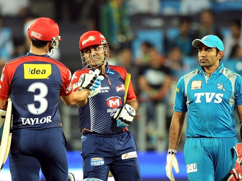 Delhi Daredevils captain Virender Sehwag (C) celebrates victory with teammate Ross Taylor as Pune Warriors India wicket-keeper Robin Uthappa (R) watches after the IPL Twenty20 cricket match in Pune. (AFP Photo/Punit Paranjpe)