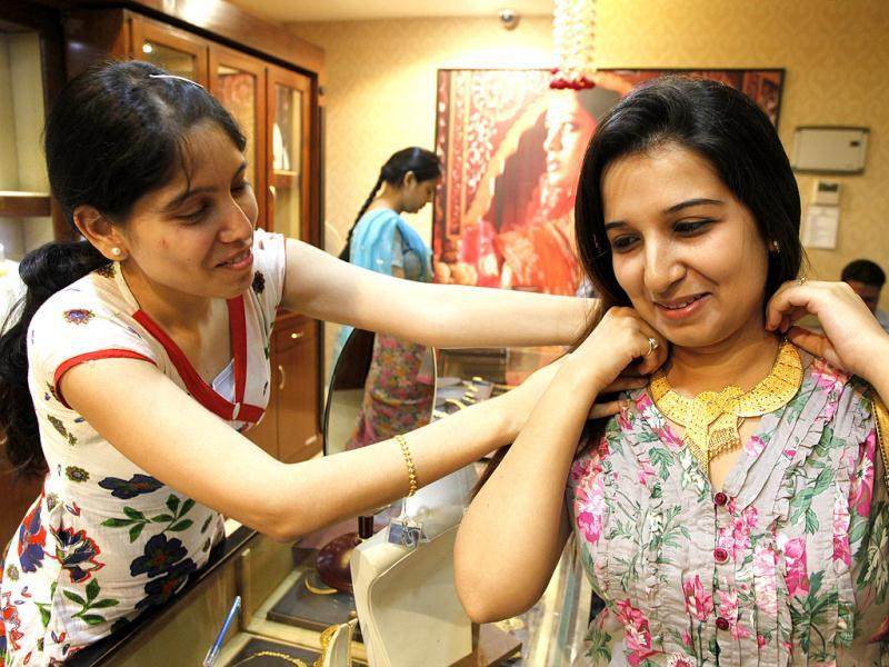 A salesclerk helps a woman wear a gold necklace at a shop in Allahabad. The Hindu festival