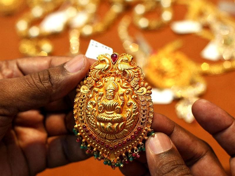 A man checks a gold ornament at a jewelry shop in Hyderabad. The Hindu festival