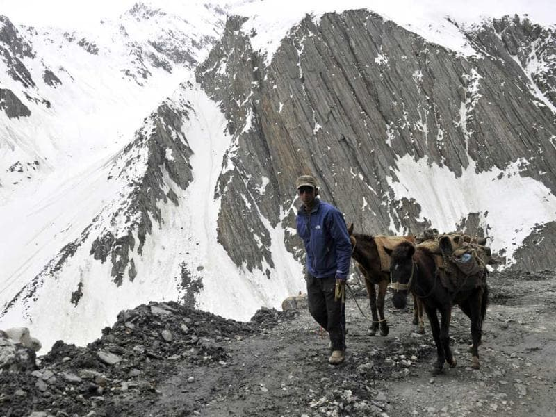 A Kashmiri porter with horses looks on from the newly-reopened Srinagar-Leh highway in Zojila Pass, about 108 km (67 miles) east of Srinagar. The 443 km (275 mile) long highway was opened for the season by Indian Army authorities after remaining snow at Zojila Pass, some 3,530 metres (11,581 feet) above sea level, had been cleared. The pass connects Kashmir with the Buddhist-dominated Ladakh region, a famous tourist destination among foreign tourists for its monasteries, landscapes and mountains. AFP PHOTO/Tauseef MUSTAFA