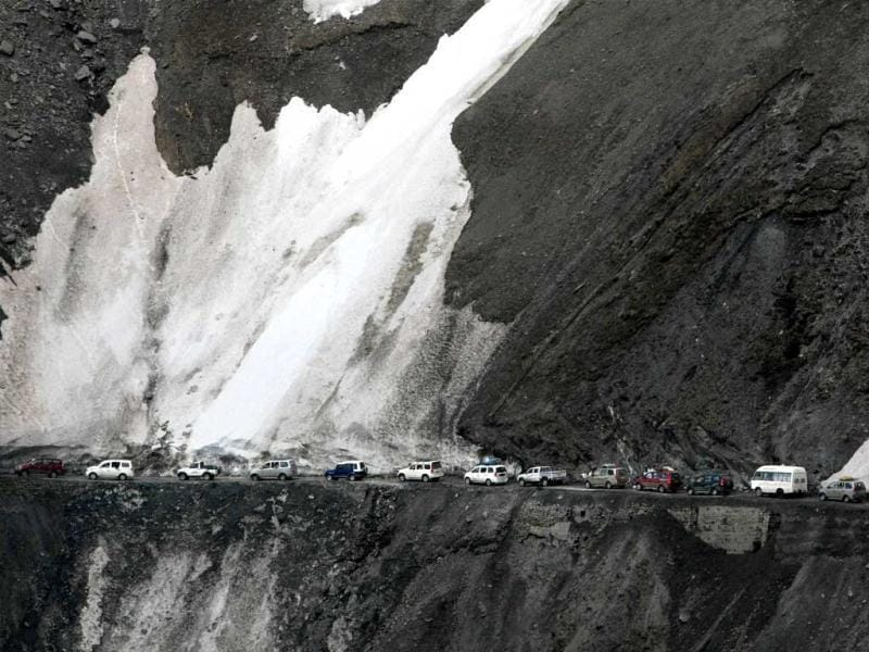 Load carriers and private taxis pass through snow-bound Zojila pass, situated at a height of 11,643 ft, as strategic Srinagar-Leh highway was opened for traffic after a nearly five-month winter break. PTI Photo by S Irfan