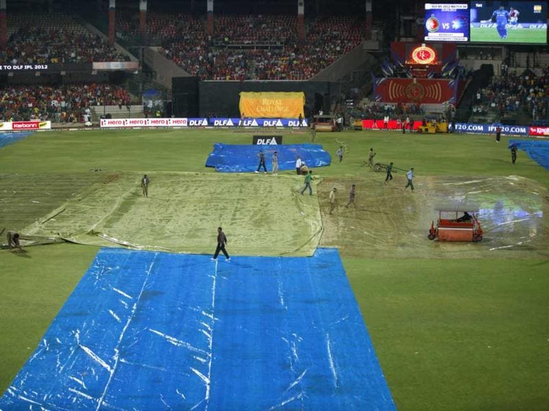 Groundsmen work to keep the field dry as rain delayed the start of the Indian Premier League (IPL) cricket match between Royal Challengers Bangalore and Chennai Super Kings' in Bangalore. (AP Photo/Aijaz Rahi)