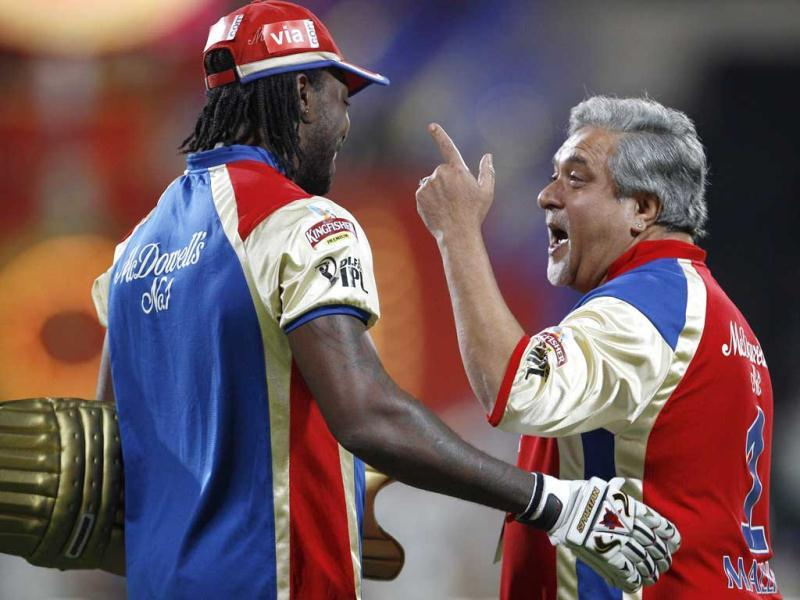 Royal Challengers Bangalore team owner Vijay Mallya, talks to cricketer Chris Gayle as rain delayed the start of the Indian Premier League (IPL) cricket match between Royal Challengers Bangalore and Chennai Super Kings' in Bangalore. (AP Photo/Aijaz Rahi)