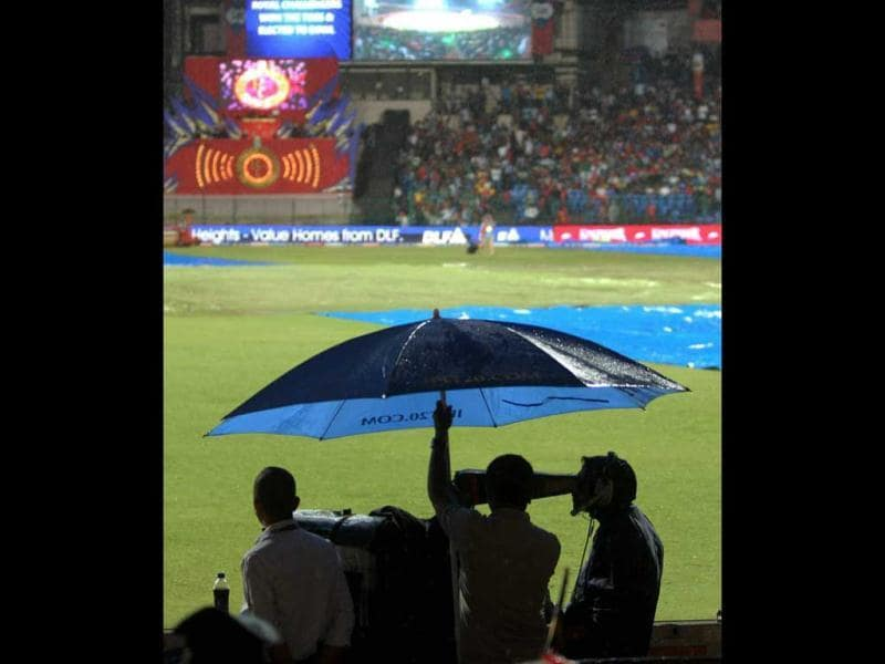 Groundsmen cover the ground with tarpaulin as it rains before the start of the match between Royal Challengers Bangalore and Chennai Super Kings at Chinnaswamy stadium in Bengaluru. (PTI Photo/Shailendra Bhojak)