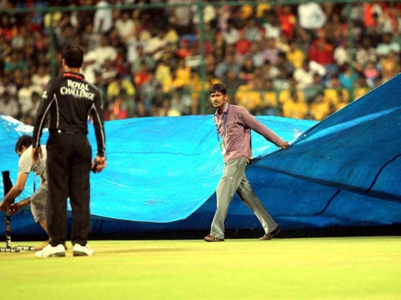 Groundsmen cover the ground with tarpaulin as it rains before the start of the match between Royal Challengers Bangalore and Chennai Super Kings at M Chinnaswamy Stadium in Bangalore. (PTI Photo/Shailendra Bhojak)