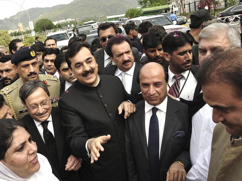 Pak PM Yousuf Raza Gilani makes his way to the Supreme Court for a hearing in Islamabad. AP Photo/BK Bangash