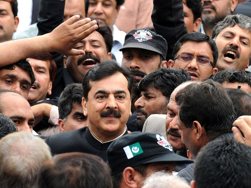 Pak PM Yousuf Raza Gilani is surrounded by security and supporters as he leaves the Supreme Court after a verdict in Islamabad. AFP Photo/Aamir Qureshi